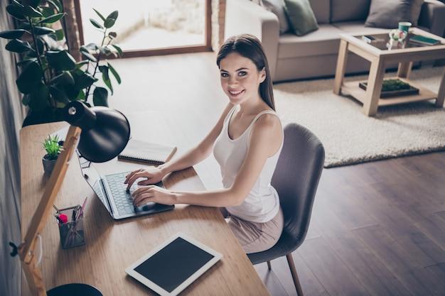 Widok z góry z góry pozytywna wesoła dziewczyna siedzieć przy biurku zdalnie