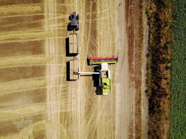 Widok z góry z latającego drona dużego profesjonalnego kombajnu ładującego pszenicę do zbiornika przyczepy-ciągnika na polu.