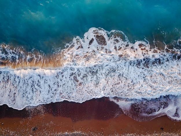 Widok z góry z latającego drona z egzotycznym krajobrazem koralowym z turkusową czystą wodą i falami zbliżającymi się do żwirowej plaży.