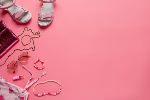 Widok z góry z letnimi ubraniami odzież dziecięca i akcesoria torba sandały szminka na różowym tle...