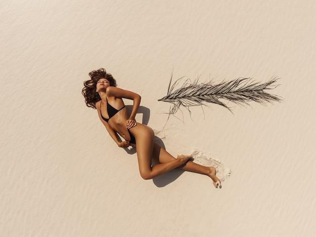 Widok z góry z lotu ptaka drone kobiety w bikini strój kąpielowy, relaks i opalanie na plaży