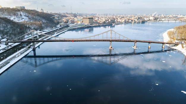 Widok z góry z lotu ptaka mostu dla pieszych w zimie i dniepr z góry, śnieg kijów gród, panoramę miasta kijów, ukraina