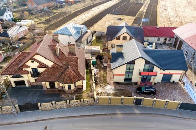 Widok z góry z lotu ptaka na przedmieściach z ładnymi domami i samochodami w słoneczny dzień.