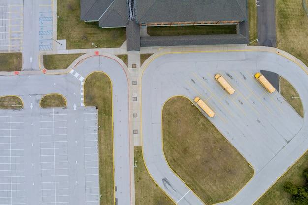 Widok z góry z lotu ptaka na żółte autobusy szkolne zaparkowane w pobliżu liceum