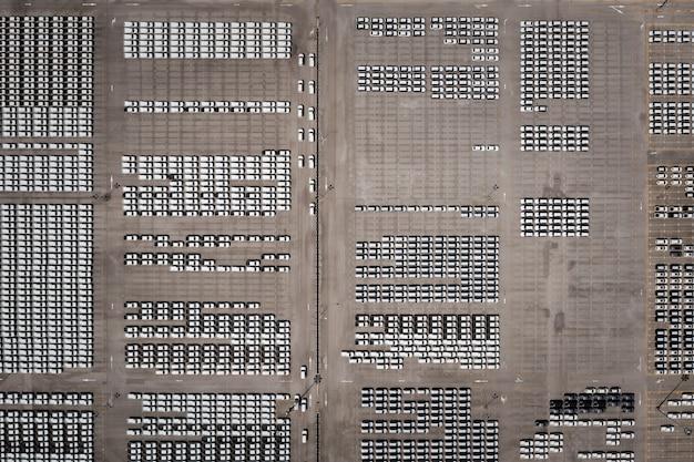Widok z góry z lotu ptaka nowe samochody ustawione w kolejce w porcie do logistyki importu i eksportu biznesu i transportu statkiem na otwartym morzu
