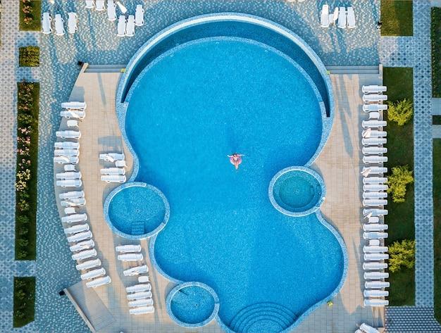 Widok z góry z lotu ptaka pięknej dziewczyny w basenie z góry, zrelaksować się popływać na nadmuchiwanym pierścieniu pączka i bawić się w wodzie na rodzinne wakacje