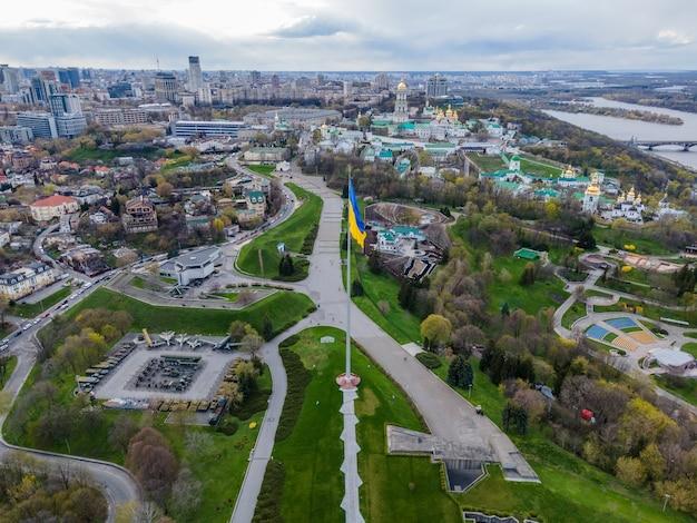 Widok z góry z lotu ptaka przez drona ukraińskiej flagi powiewającej na wietrze przeciwko miastu kijów ukraina