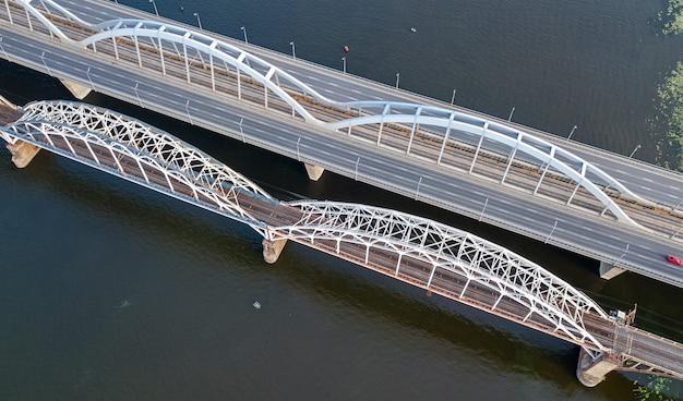 Widok z góry z lotu ptaka samochód i kolejowy most darnitsky przez rzekę dniepr z góry, panoramę miasta kijów (kijów), ukraina