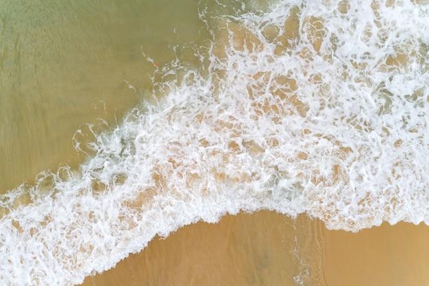 Widok z góry z lotu ptaka tropikalna plaża fala morska pluskająca na piaszczystym brzegu biała morska piana.