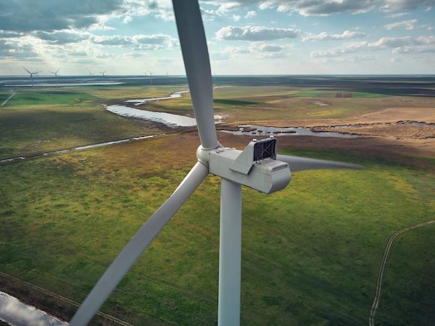 Widok z góry z lotu ptaka turbin wiatrowych i pola rolnictwa w pobliżu morza o zachodzie słońca