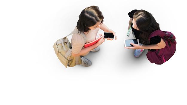 Widok z góry z lotu ptaka z dwiema studentkami ze stojakiem na smartfona na ulicy białego chodnika