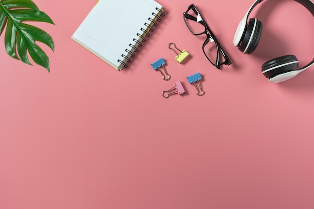 Widok z góry z okularami, książki pamiętać i słuchawki na różowym backgroup. zaśmiecone miejsce na biurku.