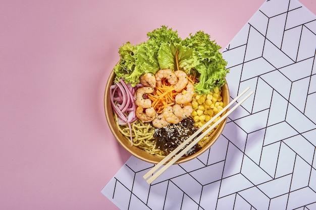 Widok z góry z organicznej miski do poke z pałeczkami umieszczonymi na teksturowanej powierzchni