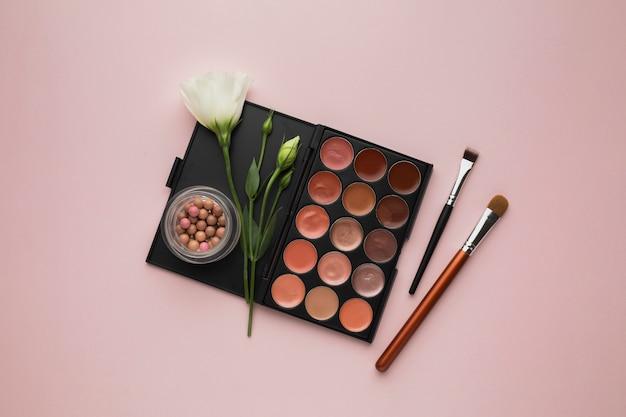 Widok z góry z paletą makijażu i różowym tłem