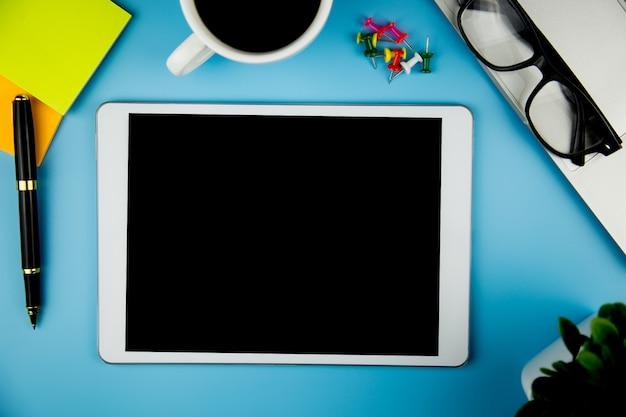 Widok z góry z pustym makieta tabletu na biurowej przestrzeni roboczej.