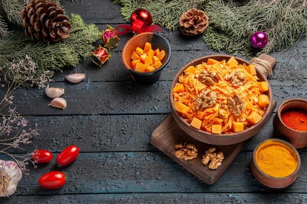 Widok z góry z tartej marchewki z przyprawami z orzechów włoskich na ciemnym biurku sałatka zdrowa dieta w kolorze orzecha