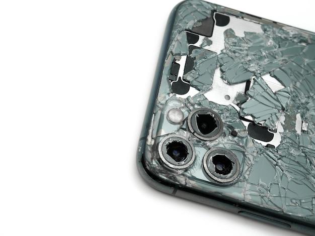 Widok z góry z tyłu nowoczesnego smartfona o północy z rozbitym szkłem i uszkodzonym aparatem z bliska na białym tle