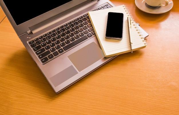 Widok z góry z urzędu drewniane, komputer pusty biały notatnik i kubek kawy