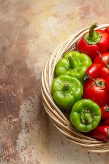 Widok z góry z zielonej i czerwonej papryki ostra papryka pomidory w wiklinowym koszu na bursztynowym tle