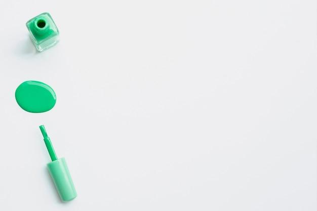 Widok z góry z zielonym lakierem do paznokci i miejscem na kopię
