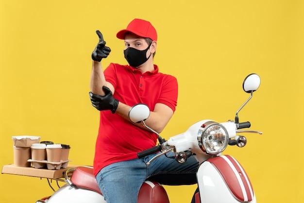 Widok z góry zadowolony, ambitny młody dorosły ubrany w czerwoną bluzkę i rękawiczki w masce medycznej dostarczający zamówienie siedząc na skuterze na żółtym tle