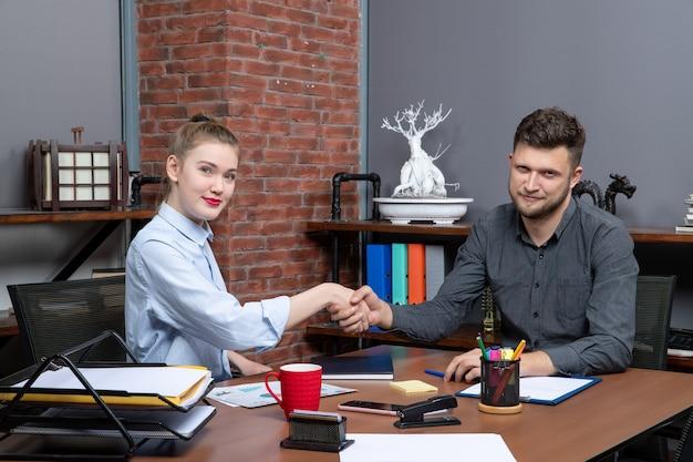Widok z góry zadowolonych i szczęśliwych pracowników biurowych siedzących przy stole w sali konferencyjnej w środowisku biurowym