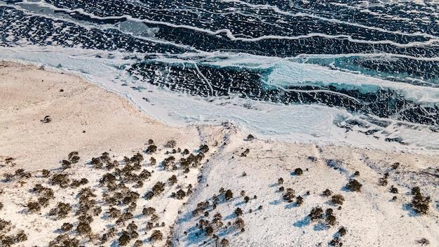 Widok z góry zamarzniętego jeziora bajkał. lód, pęknięcia, śnieg, brzeg, drzewa. obwód irkucki, rosja
