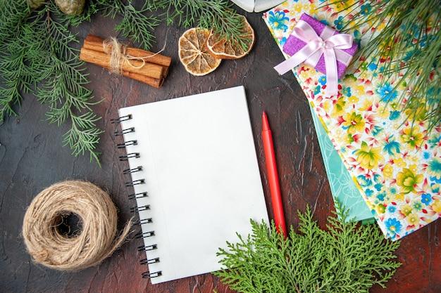 Widok z góry zamkniętego notatnika z długopisowymi limonkami cynamonowymi kulką gałęzi jodły linowej i książkami na ciemnym tle