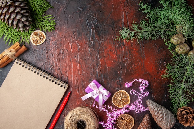 Widok z góry zamkniętego notatnika z limonkami cynamonowymi pióra i kulką szyszek iglastych prezentowych na ciemnym tle