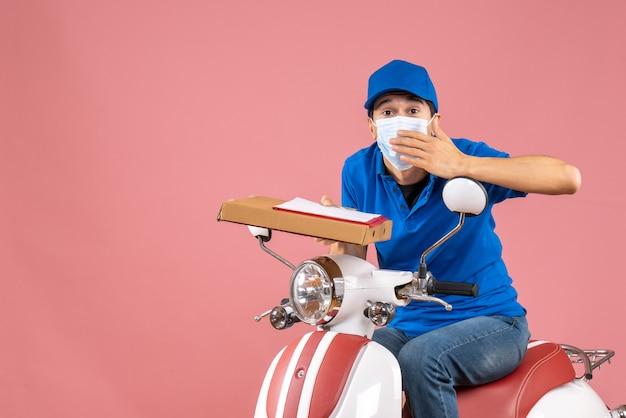Widok z góry zaniepokojonej męskiej dostawy w masce w kapeluszu siedzącej na skuterze dostarczającej zamówienia z dokumentem na brzoskwiniowym tle