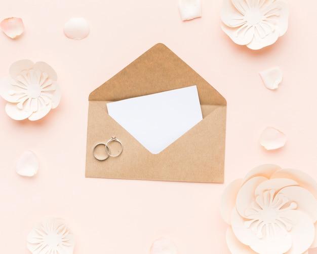 Widok z góry zaproszenie na ślub z pierścionkami zaręczynowymi