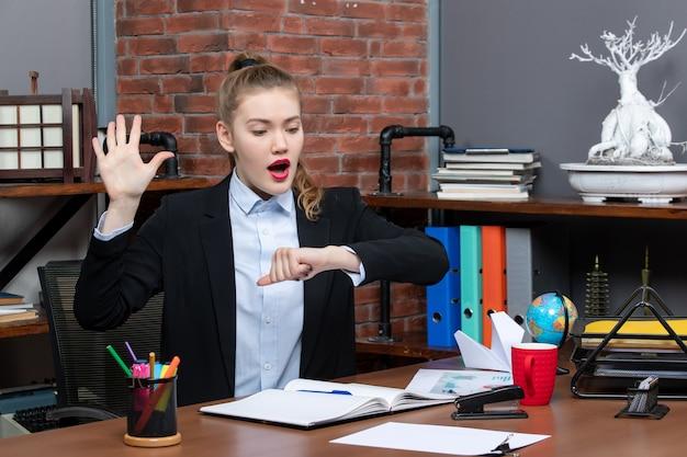 Widok z góry zaskoczonej młodej kobiety siedzącej przy stole i sprawdzającej swój czas w biurze