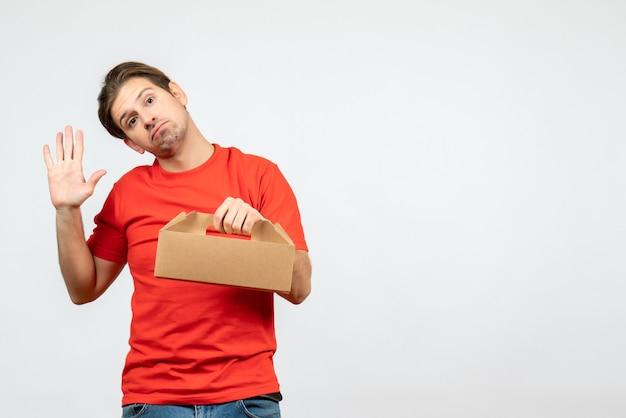 Widok z góry zaskoczony i zszokowany młody człowiek w czerwonej bluzce, trzymając pudełko pokazujące pięć na białej ścianie