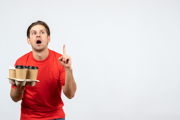 Widok z góry zaskoczony młody człowiek w czerwonej bluzce, trzymając zamówienia i skierowany w górę na białej ścianie