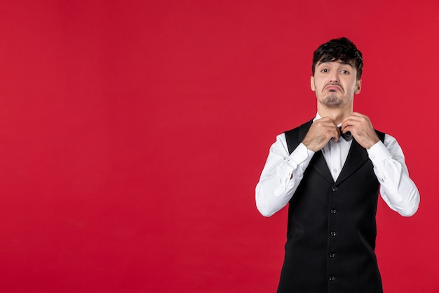Widok z góry zastanawiającego się, ciekawego męskiego kelnera w mundurze z muszką