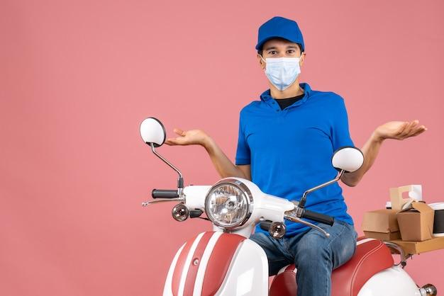 Widok z góry zastanawiającego się kuriera w masce medycznej w kapeluszu siedzącym na skuterze na pastelowej brzoskwini