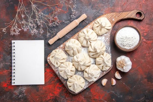 Widok z góry zbliżenie chinkali apetyczny chinkali na pokładzie czosnek miska mąki notebook
