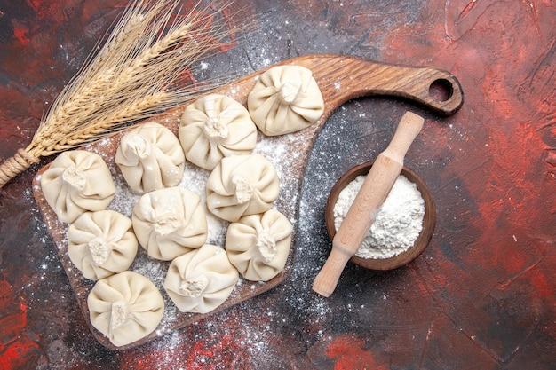 Widok z góry zbliżenie chinkali chinkali na desce do krojenia uszy pszenicy wałek do ciasta mąki