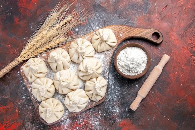 Widok z góry zbliżenie chinkali dziesięć chinkali na desce do krojenia uszy pszenicy wałek do ciasta mąki