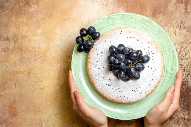 Widok z góry zbliżenie ciasto zielony talerz apetyczny ciasto z winogronami w rękach