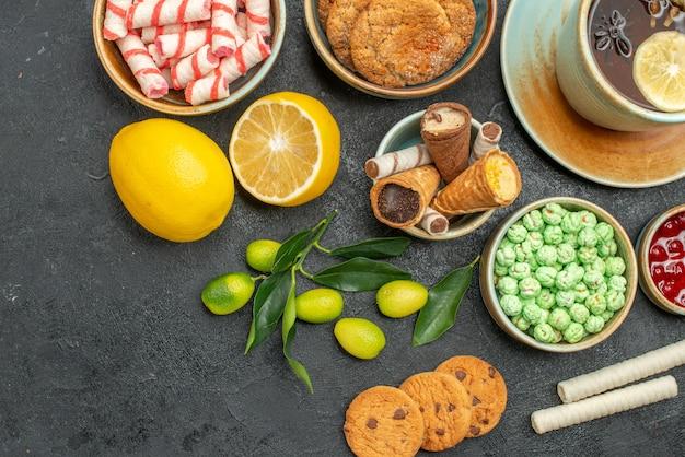 Widok z góry zbliżenie filiżanka herbaty cytryna owoce cytrusowe filiżanka herbaty ziołowej słodycze ciasteczka dżem