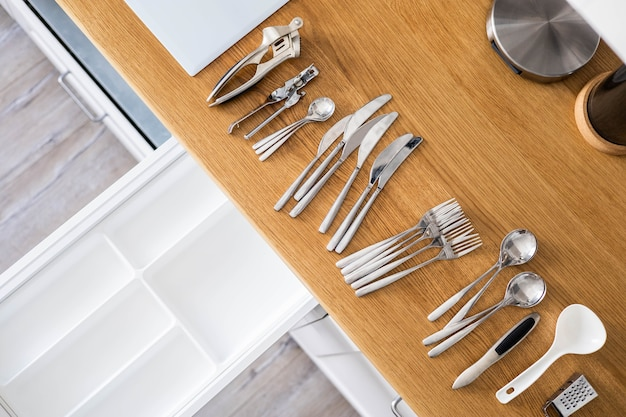 Widok z góry zbliżenie gospodyni ręce sprzątanie sztućców w szufladzie ogólne sprzątanie w kuchni