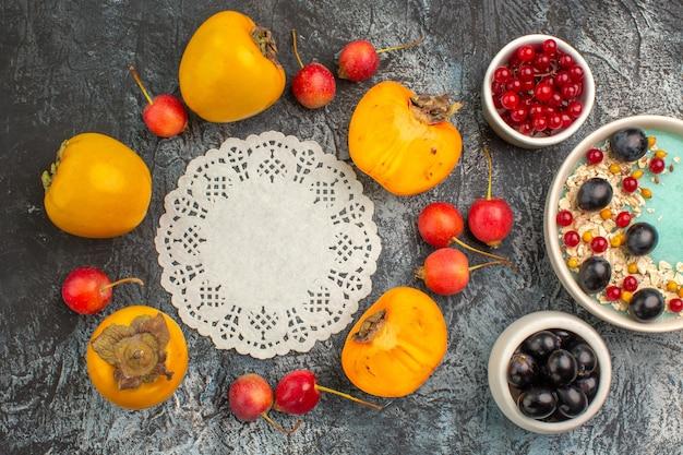 Widok z góry zbliżenie jagody miski czerwonych porzeczek winogron wiśni persimmons wokół koronki serwetka