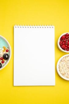 Widok z góry zbliżenie jagody miski kolorowych jagód płatki owsiane biały notatnik