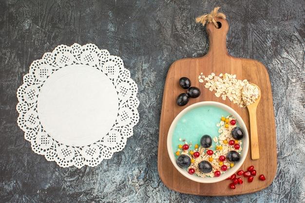 Widok z góry zbliżenie jagody płatki owsiane winogrona łyżka na serwetka koronki cięcia deska do krojenia
