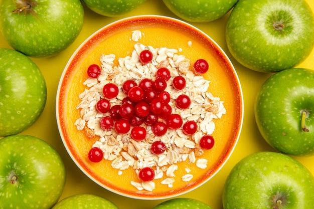 Widok z góry zbliżenie jagody zielone jabłka miska jagód płatki owsiane na stole