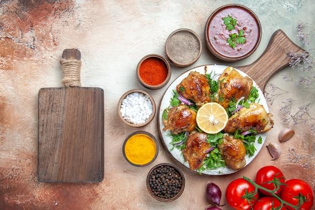 Widok z góry zbliżenie kurczaka kurczak z ziołami cytryna pomidory sos przyprawami deska do krojenia