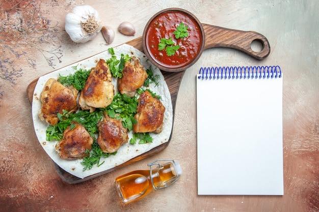 Widok z góry zbliżenie kurczaka kurczak z ziołami miska sosu butelka oleju czosnku biały notatnik