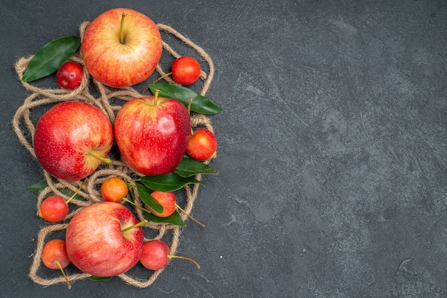 Widok z góry zbliżenie owoce wiśnie liny czerwono-żółte jabłka z liśćmi