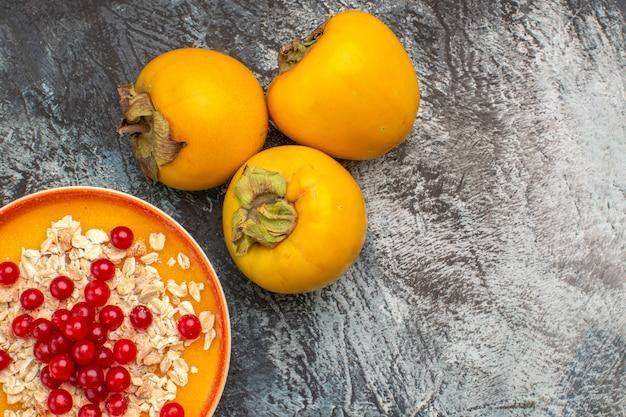 Widok z góry zbliżenie persimmons miska jagód trzy persimmons